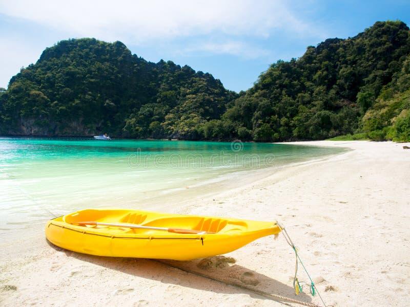 在白色沙子海滩的黄色皮船小船在海 库存照片
