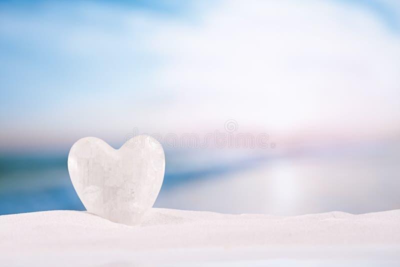在白色沙子海滩的白色水晶心脏 库存照片