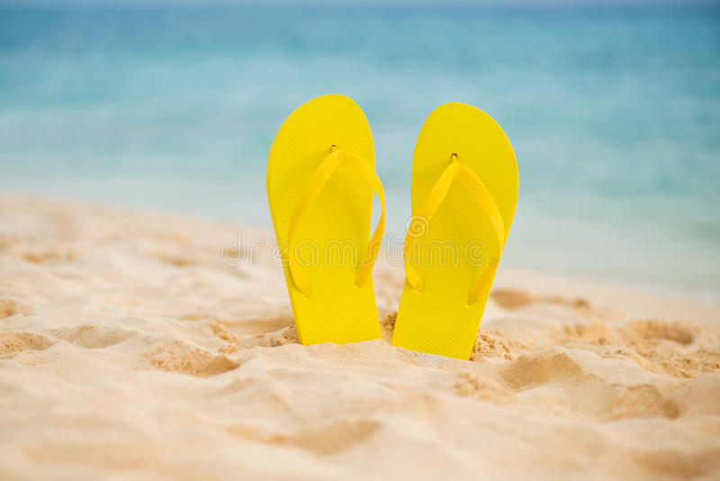 在白色沙子海滩的黄色凉鞋触发器有蓝色海和天空背景在暑假复制空间 库存照片