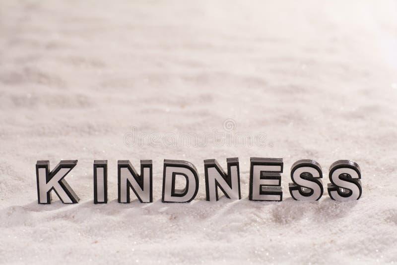 在白色沙子的仁慈词 免版税图库摄影