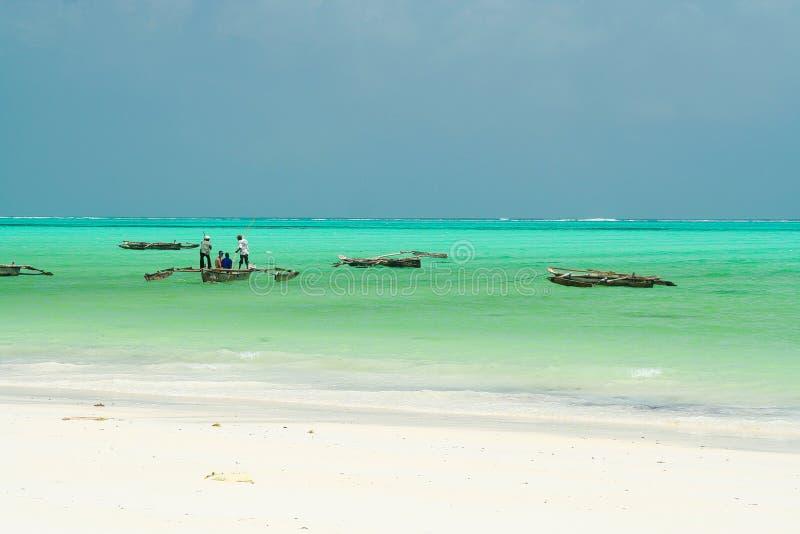 在白色沙子的全景不尽的看法在与木传统dau帆船的绿松石绿色水-帕杰海滩,桑给巴尔 免版税库存照片
