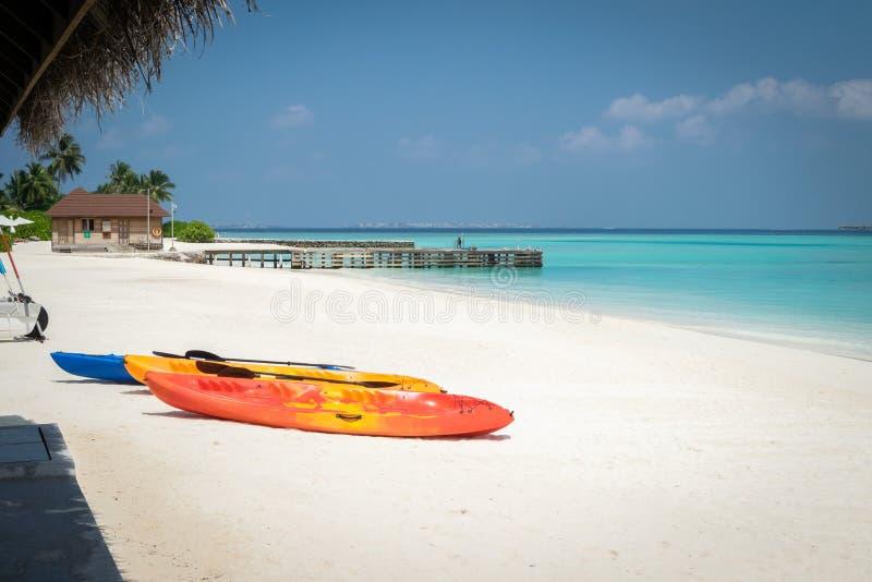 在白色沙滩的三个独木舟,在绿松石盐水湖的石码头在马尔代夫 免版税库存照片