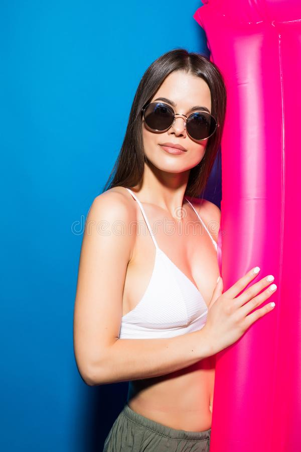 在白色泳装打扮的一名激动的年轻微笑的妇女的画象摆在与桃红色可膨胀的床垫被隔绝在蓝色backg 库存图片
