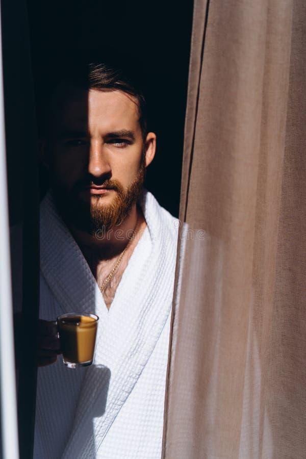 在白色浴巾的男性有咖啡杯的在手中 图库摄影