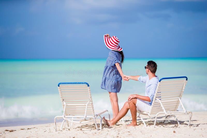 在白色海滩的年轻夫妇在暑假时 愉快的家庭享受他们的蜜月 免版税库存照片