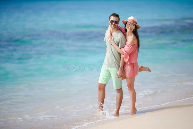 在白色海滩的年轻夫妇在暑假时 愉快的家庭享受他们的蜜月 免版税库存图片