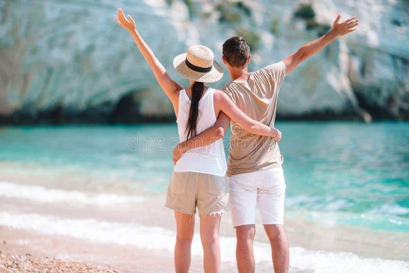 在白色海滩的年轻夫妇在暑假时 库存图片