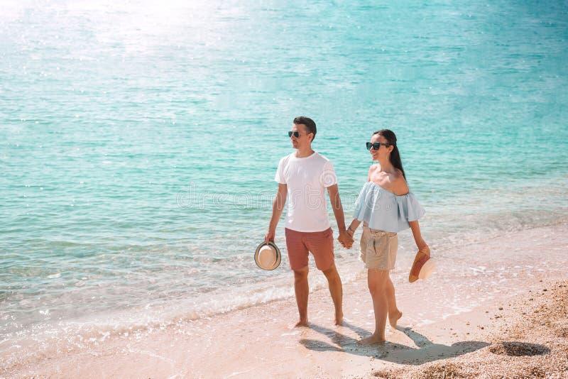 在白色海滩的年轻夫妇在暑假时 图库摄影