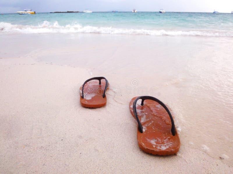 在白色海滩的凉鞋 免版税库存照片