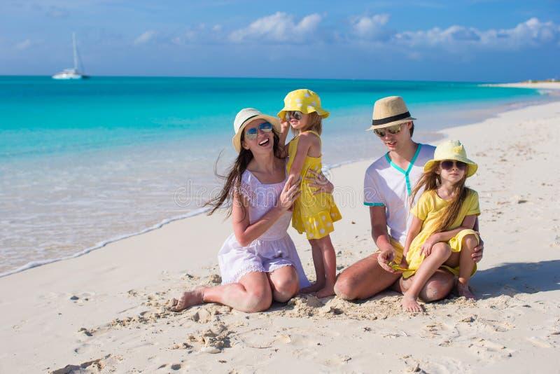 在白色海滩的愉快的年轻家庭在暑假时 库存图片