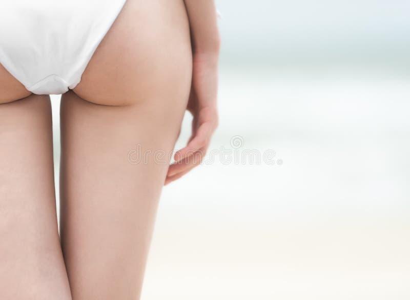 在白色游泳衣的年轻性感的妇女后侧方。 免版税库存图片