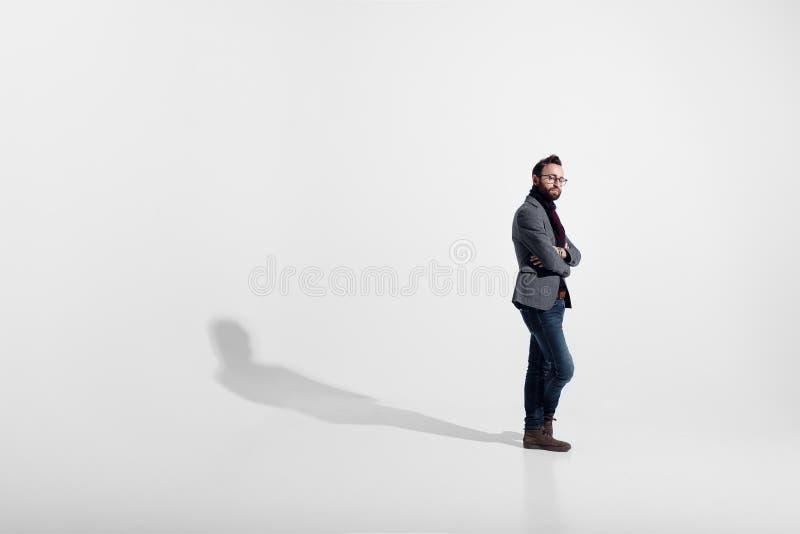 在白色演播室背景隔绝的时髦的人,镜片,站立的充分的高度,当横渡的胳膊,看照相机 库存照片