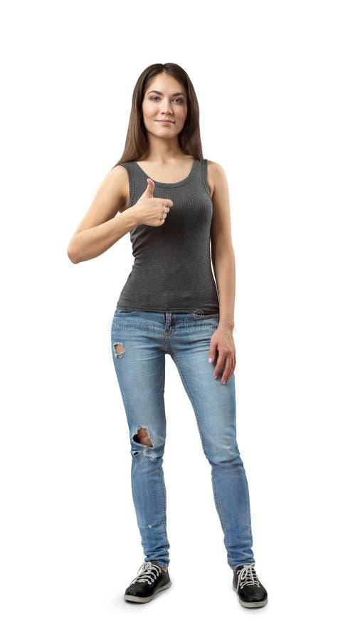 在白色灰色无袖的上面和蓝色牛仔裤身分和givng翘拇指的年轻美丽的微笑的妇女隔绝的 库存图片