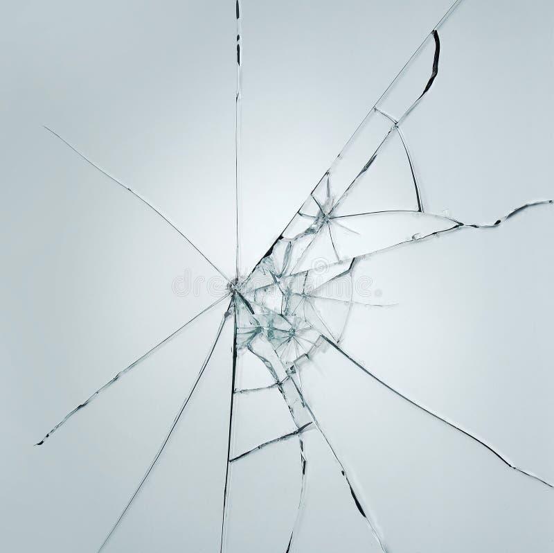 在白色灰色背景的残破的玻璃窗裂缝 免版税库存照片