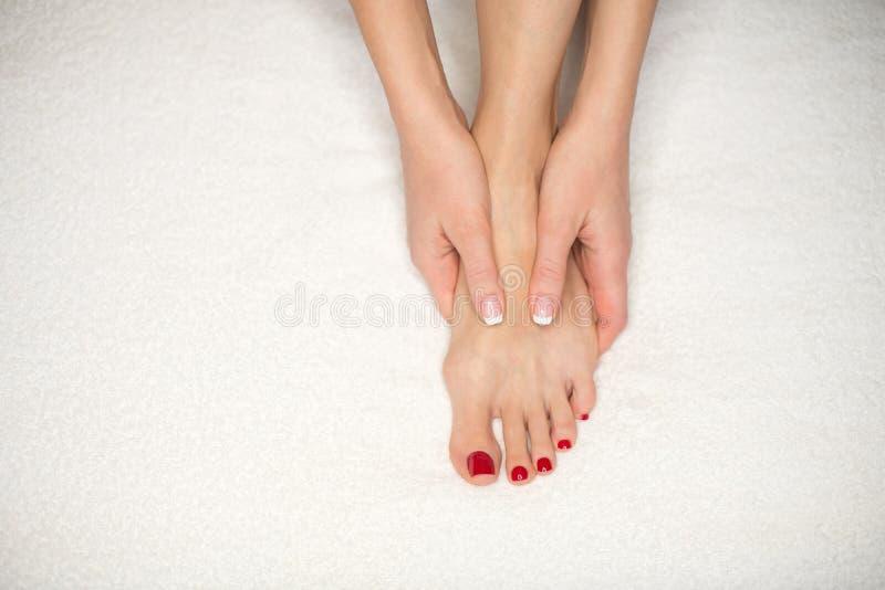 在白色特里毛巾和手的女性脚 妇女拿着她的脚底并且由她的手指集合它 经典法式修剪和 图库摄影