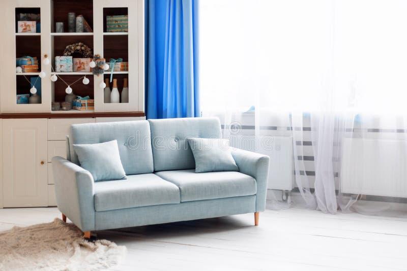 在白色现代内部的蓝色沙发与圣诞节装饰 库存图片