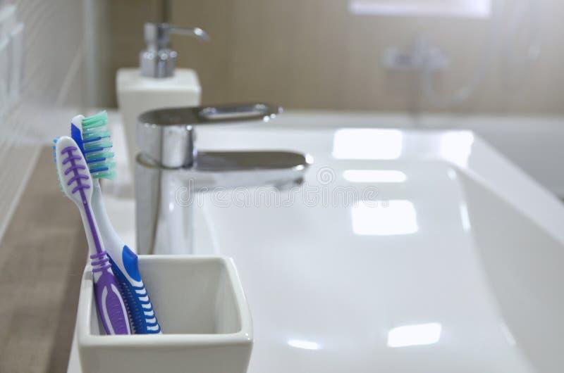 在白色玻璃与和肥皂分配器的牙刷在卫生间特写镜头 库存照片