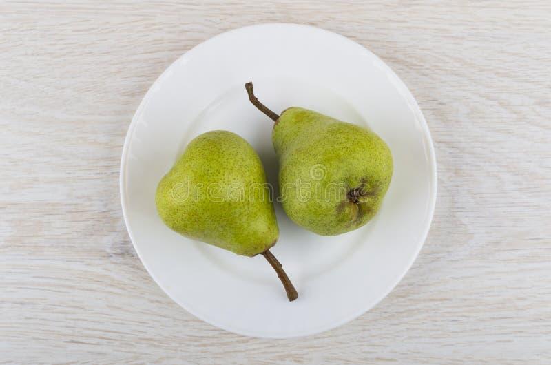 在白色玻璃板的两个绿色梨在木桌上 库存图片