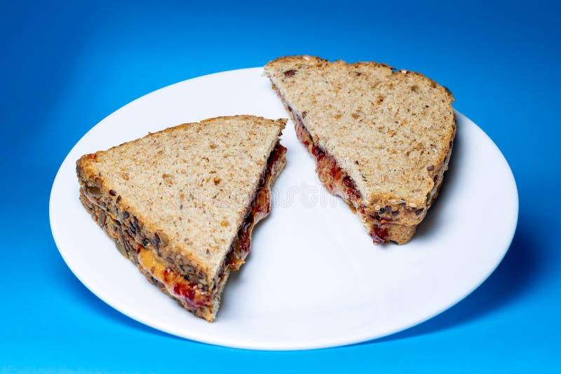 在白色玻璃板的花生酱和果冻三明治 库存图片