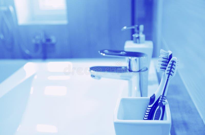 在白色玻璃的牙刷与在卫生间特写镜头,全部在蓝色口气 免版税库存照片