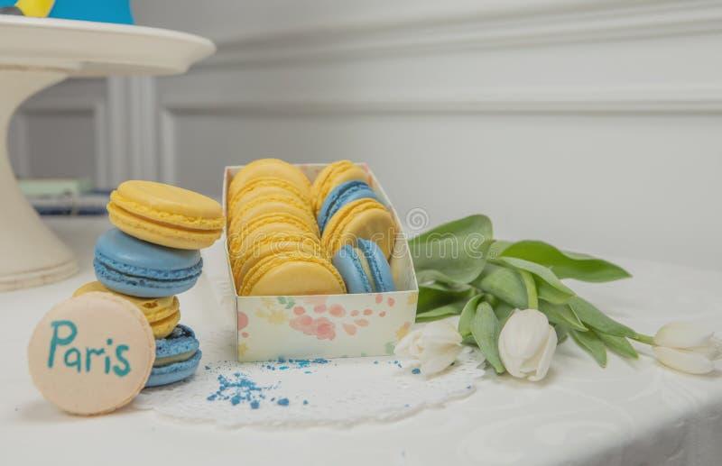 在白色白色背景的甜法国蛋白杏仁饼干 飞行落的甜通心面 免版税图库摄影