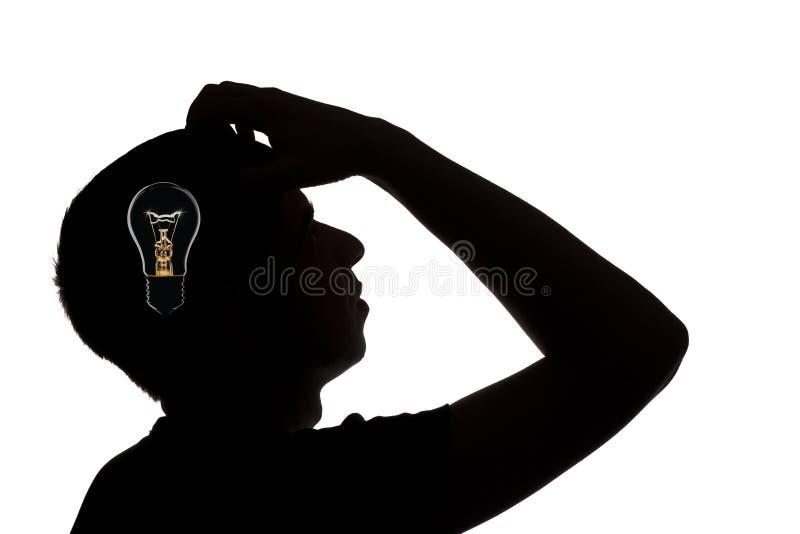 在白色的一个想法破晓人的剪影隔绝了背景,概念被认为的电灯泡 库存照片