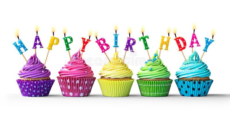在白色的五颜六色的生日杯形蛋糕 库存图片