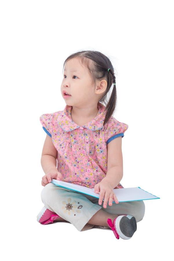 在白色的小的亚洲女孩阅读书 图库摄影