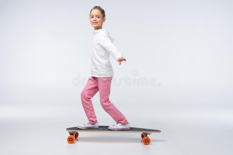 在白色的微笑的女孩骑马滑板 库存照片