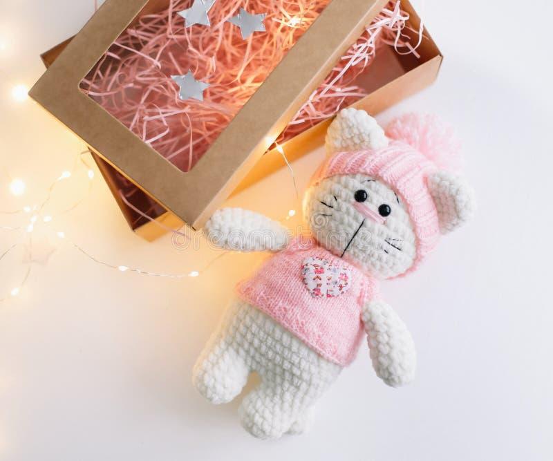 在白色的手工制造被编织的玩具猫 Hello Kitty 平的位置,顶视图 免版税库存图片