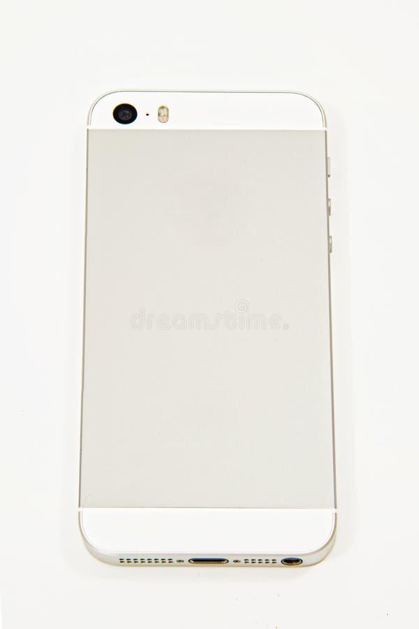 在白色的白色和银色智能手机后面 库存照片