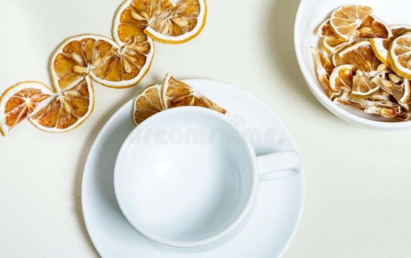 在白色的空的白色杯子 在一白色碗和forcground的干柠檬切片 免版税图库摄影