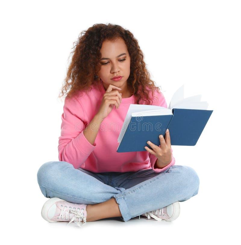 在白色的美丽的非裔美国人的妇女看书 免版税图库摄影