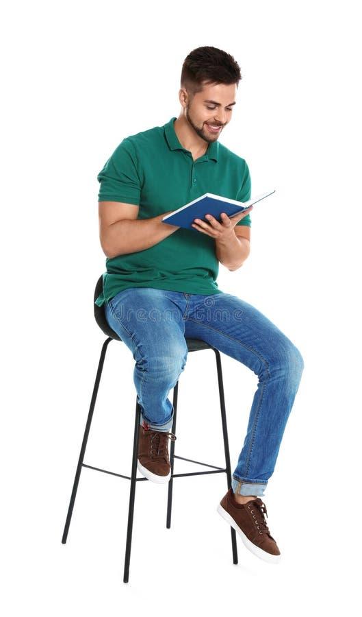 在白色的英俊的年轻人看书 图库摄影