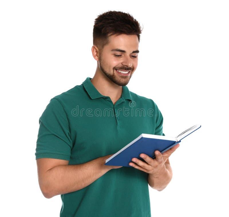 在白色的英俊的年轻人看书 免版税库存图片