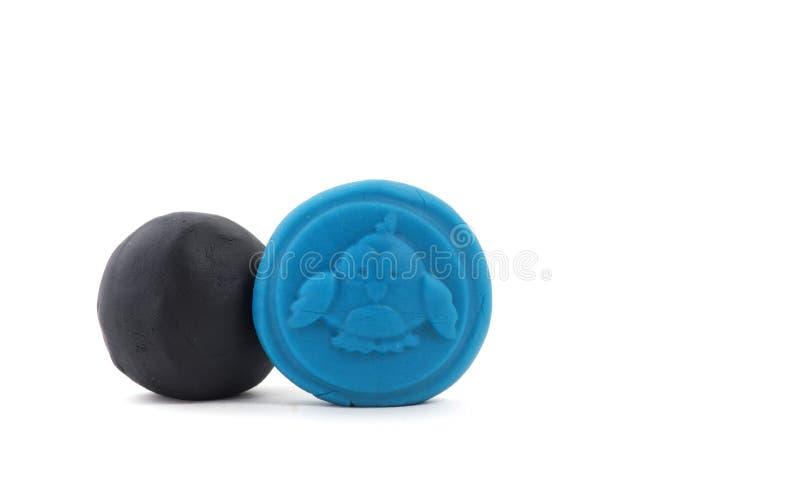 在白色的蓝色和黑彩色塑泥小雕象 免版税库存图片