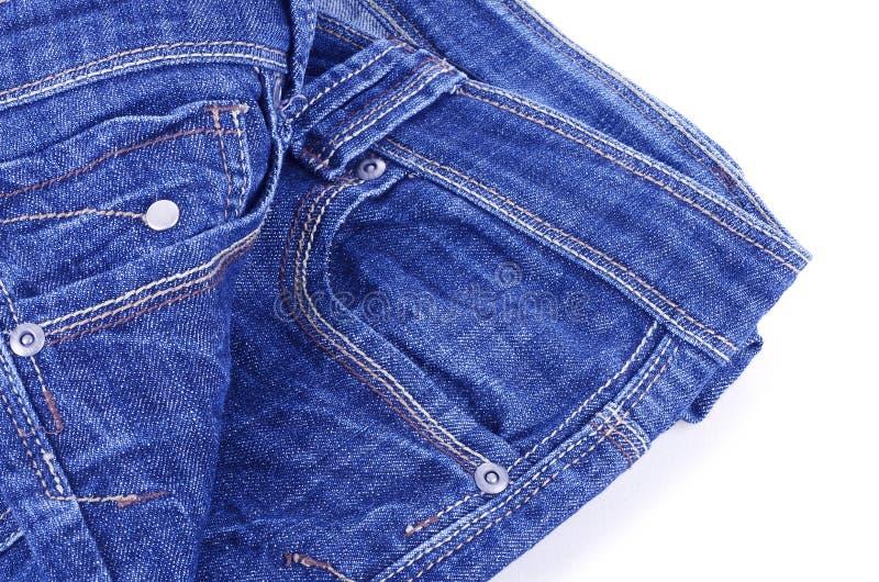 在白色的蓝色牛仔裤 免版税库存照片
