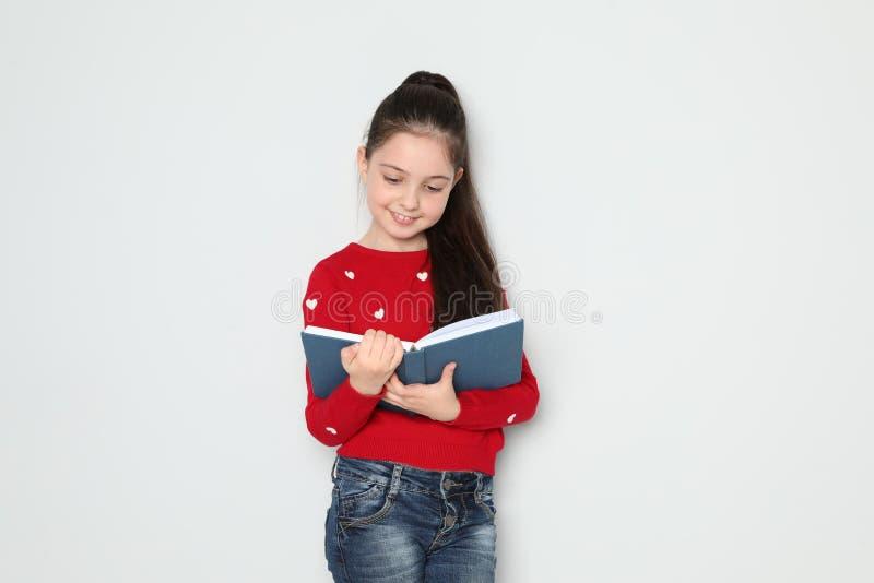 在白色的逗人喜爱的女孩看书 图库摄影