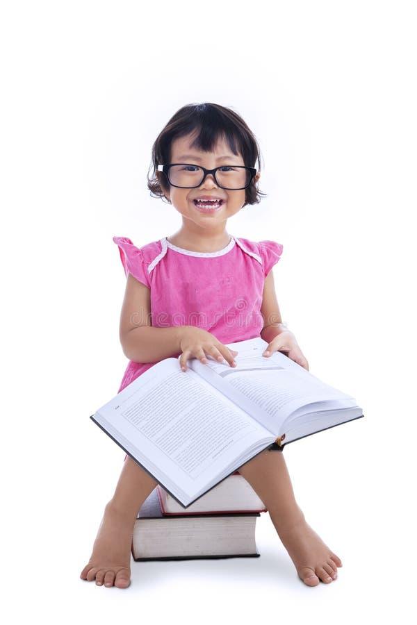 在白色的逗人喜爱的女孩阅读书 免版税库存照片