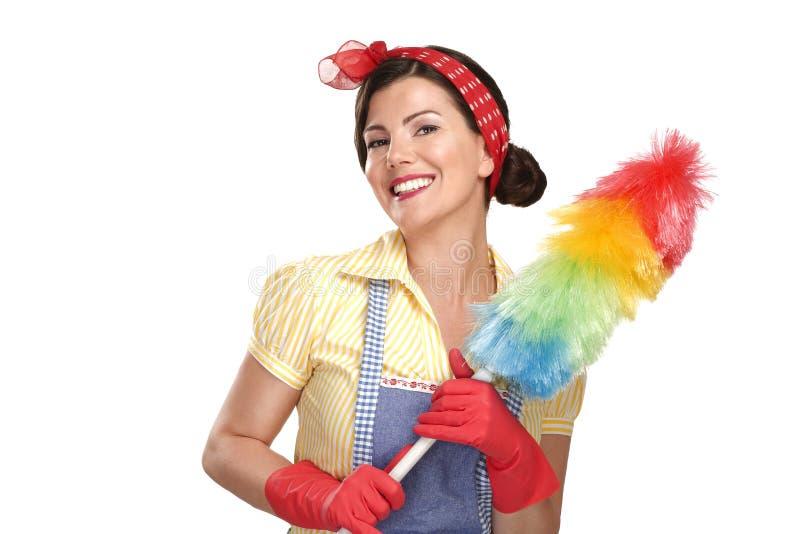 在白色的年轻愉快的美丽的妇女佣人打扫灰尘 免版税库存图片
