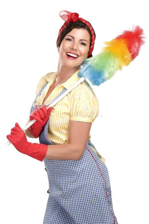 在白色的年轻愉快的美丽的妇女佣人打扫灰尘 库存照片