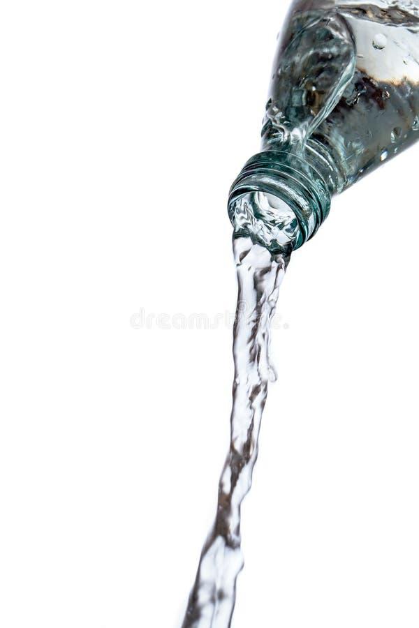 在白色的玻璃瓶puring的水 免版税库存照片
