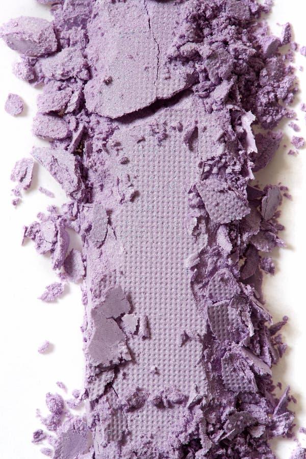 在白色的紫罗兰色眼影被击碎的宏指令 库存照片