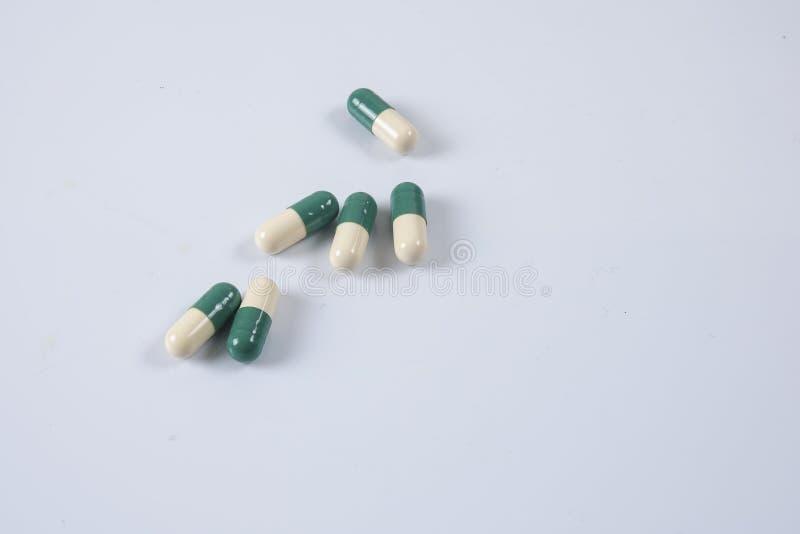在白色的黄色/绿色医学药片 概念性的医疗保健 免版税库存图片
