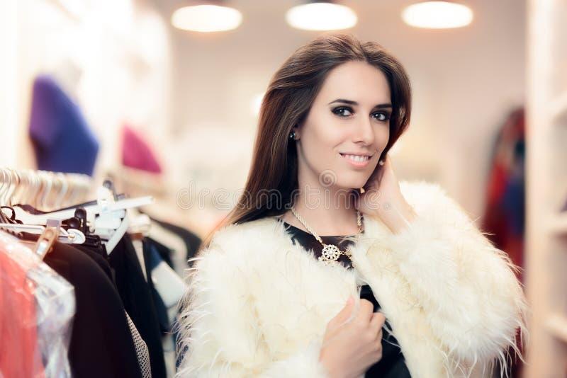 在白色皮大衣打扮的购物妇女在时尚商店 免版税库存图片