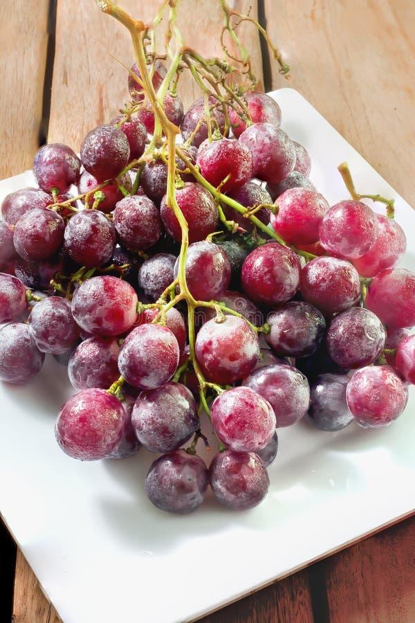 在白色盘和木桌的新鲜的红葡萄 图库摄影
