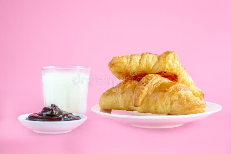 在白色盘和杯的两个新月形面包在桃红色后面地面的新鲜的牛奶与您的文本的拷贝空间 早餐概念 免版税图库摄影