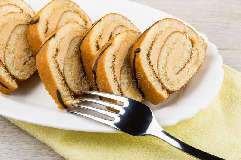 在白色盘的卷蛋糕蛋糕在黄色毛巾 库存图片