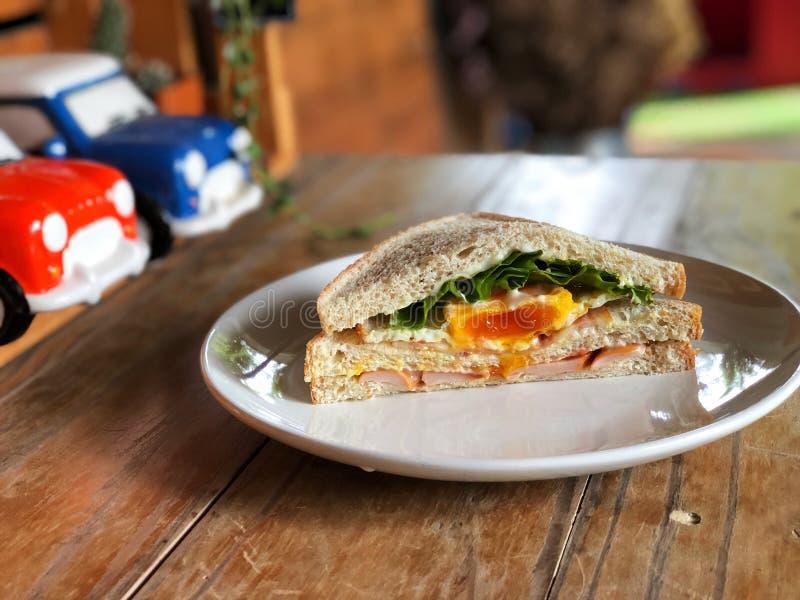 在白色盘的新鲜的三明治在与自然光,可口早餐的木桌上 库存照片
