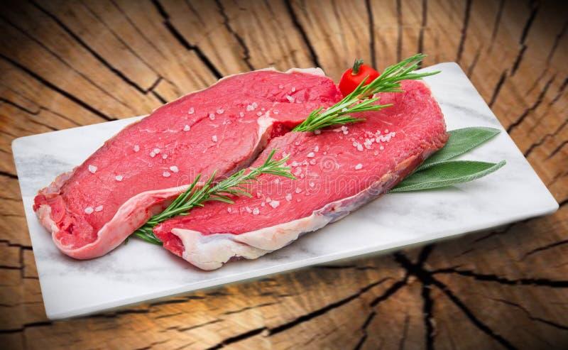 在白色盘的未加工的牛排肉有树干背景 免版税库存照片
